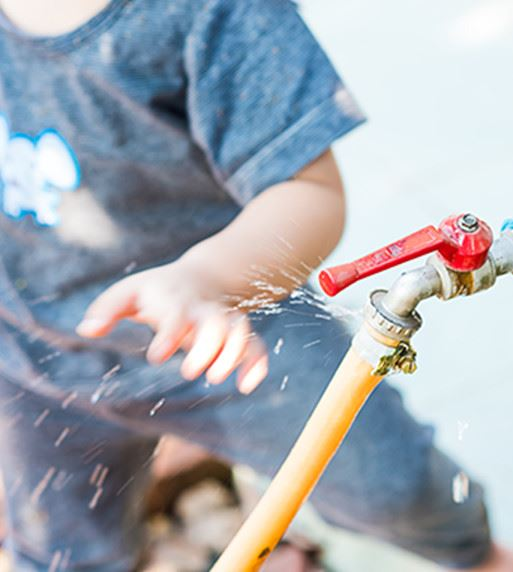 A child playing with water coming out of a hose